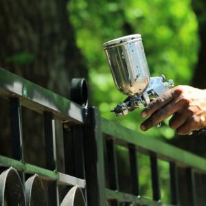 Man Spraying Vector Fence: Hand Spraying A Black Paint In Slow Motion On The Fence In The Park Sznebzjujmd