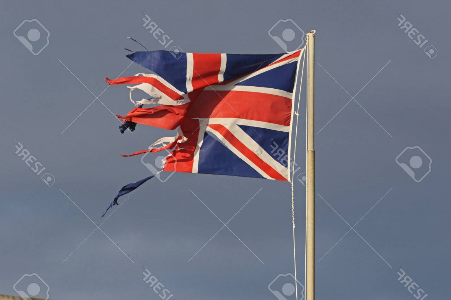 Union Jack Flag Tattered Vector: Photoweather Worn British Flag Or Union Jack Torn And Tattered Flying In The Winter By The Sea In Italy
