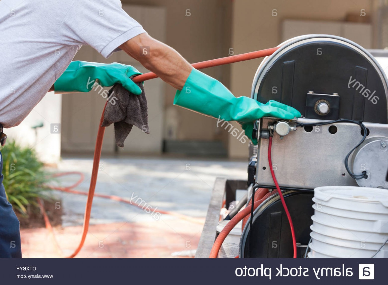 Vector Control Technician: Stock Photo Pest Control Technician Pulling Hose From Reel In Service Truck
